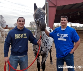 2nd Lt. Zachary Duncavage, USMC, left, handles mascot Xena during a visit to All Xena's Horses with brother Luke, right, currently finishing his last year at the United States Air Force Academy.