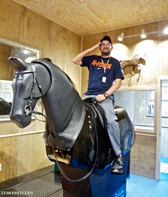 Marine Corps veteran Steven Schulz salutes from aboard Xena, the fully interactive riding simulator, during a visit to The Xena Project on October 1st, 2014. Schulz, who incurred Traumatic Brain Injury and associated paralysis while serving in Iraq, worked on balance, coordination, and posture during his session, funded by private donation from a Vietnam veteran. Learn more about The Xena Project, where veterans serve veterans and horses heal everyone, at xenahorse.com (Photo by The Xena Project / RELEASED)