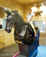 Ms. Lou Hutchison, the youngest member of the San Jacinto Pony Club, rides the simulator during a visit to All Xena's Horses on June 22nd, 2014.  The fully interactive simulator is one of only a few in the U.S., and is also used for therapeutic work.  (Photo by Jan Shultis, All Xena's Horses / RELEASED).
